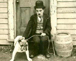 "Charlie Chaplin in ""The Kid."" The film debuted in 1921 and was written and directed by Chaplin."