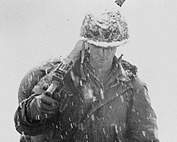 An American soldier holding a weapon while snow falls